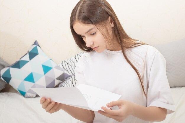Notícias inesperadas. garota lendo uma carta em uma folha de papel em casa, analisa o texto com atenção