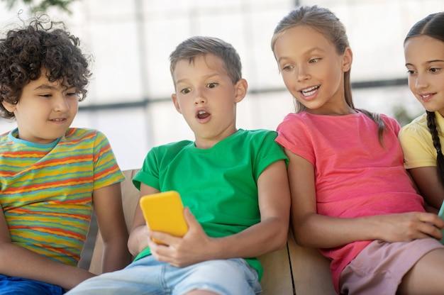 Notícias inesperadas. menino surpreso com a boca aberta olhando para o smartphone e amigos passando os momentos de lazer de verão juntos