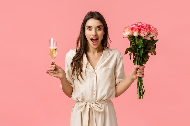 Notícias maravilhosas, celebração e conceito de emoções. alegre mulher morena atraente vestido, espalhe as mãos para o lado surpreso e se perguntou, boca aberta ofegante, segure a taça de champanhe e flores