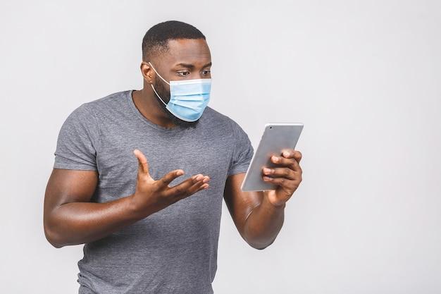 Notícias médicas! homem afro-americano com máscara médica estéril segurando tablet digital