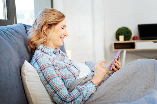 Notícias no smartphone. mulher bonita e radiante, de cabelo claro, satisfeita ao lidar com o smartphone