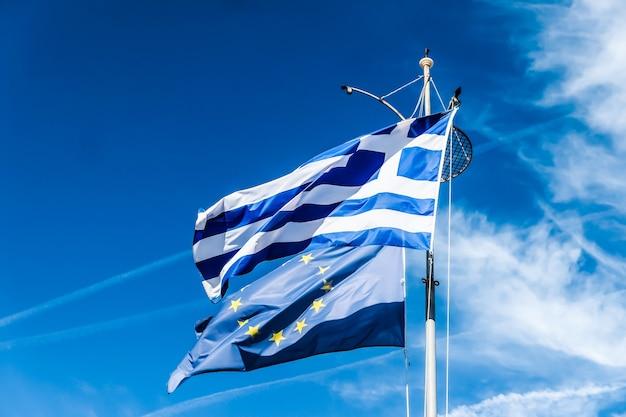 Notícias políticas europeias bandeiras de conceito de grexit e nação da grécia e da união europeia na política de fundo do céu azul da europa