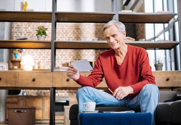 Notificação agradável. homem idoso simpático, positivo, segurando uma nota e sorrindo enquanto está sentado à mesa