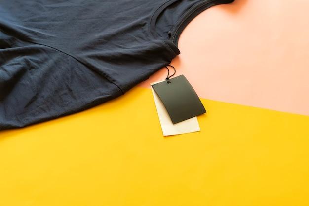 Nova camiseta casual com preço de venda com espaço de cópia isolado no fundo rosa e amarelo.