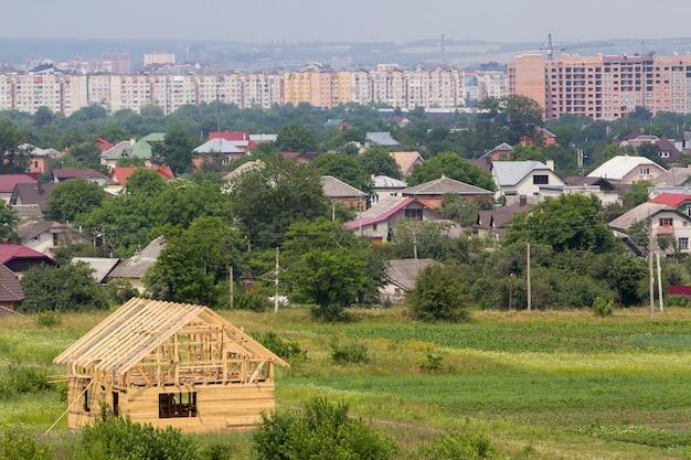 Nova casa de campo de madeira de materiais naturais de madeira em construção no bairro tranquilo, no fundo de edifícios da cidade distante. propriedade, investimento, conceito profissional de construção e reconstrução.