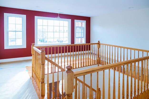 Nova casa de construção com escada de madeira com grades de madeira e pisos de madeira.