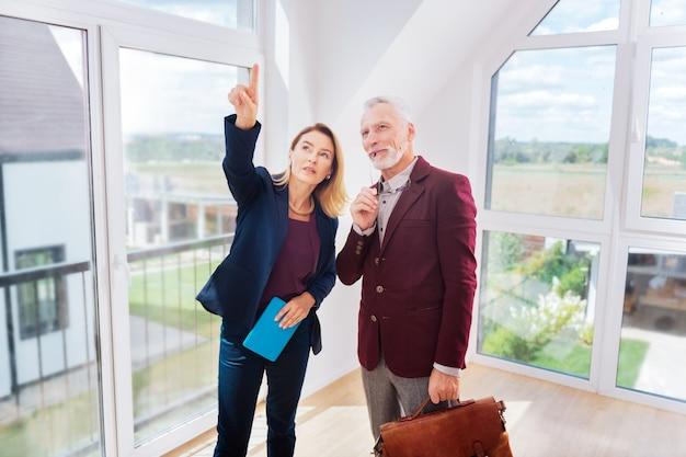 Nova casa. homem de negócios rico e barbudo sentindo curiosidade ao pensar em comprar uma casa nova perto de um corretor de imóveis