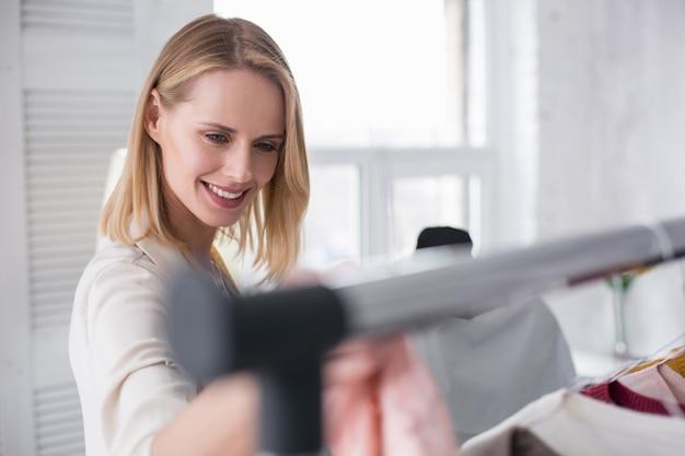 Nova coleção. mulher de negócios feliz e alegre posando em um fundo desfocado enquanto sorri