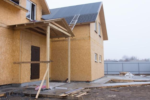 Nova construção de casa de madeira em construção com uma escada no telhado para instalar as telhas e um pátio lamacento esperando para ser ajardinado