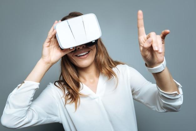 Nova dimensão. mulher alegre feliz e positiva apontando com o dedo e sorrindo enquanto usava óculos 3d