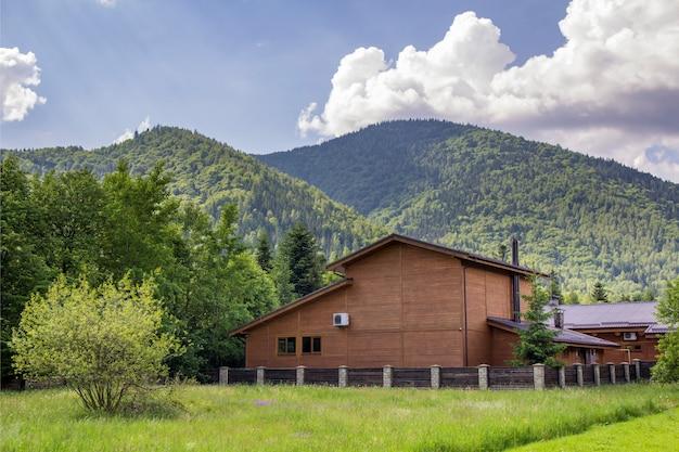 Nova e agradável casa de madeira com dois andares e ar-condicionado, atrás da cerca de tijolos de pedra no prado gramado.