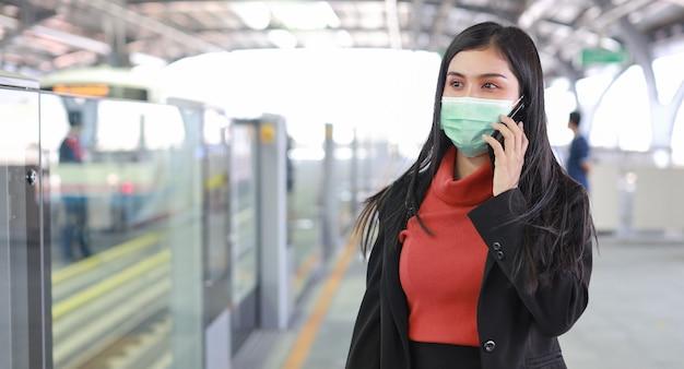Nova epidemia normal de covid-19, jovem empresária asiática usando máscara de proteção para prevenir o vírus covid-19 ou infecção por coronavírus de pessoas no trem, usando comunicação por smartphone no trem
