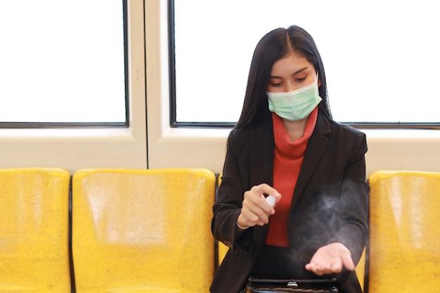 Nova epidemia normal de covid-19, jovem empresária inteligente asiática usando máscara de proteção para evitar o vírus covid-19 ou infecção por coronavírus de pessoas no trem, usando álcool em spray desinfetante para as mãos