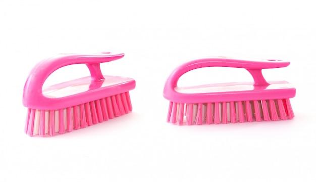 Nova escova de piso plástica rosa sobre fundo branco.