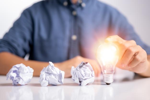 Nova ideia e conceito de lâmpada com a mão do homem tocando a lâmpada e três papéis de escritório amassados