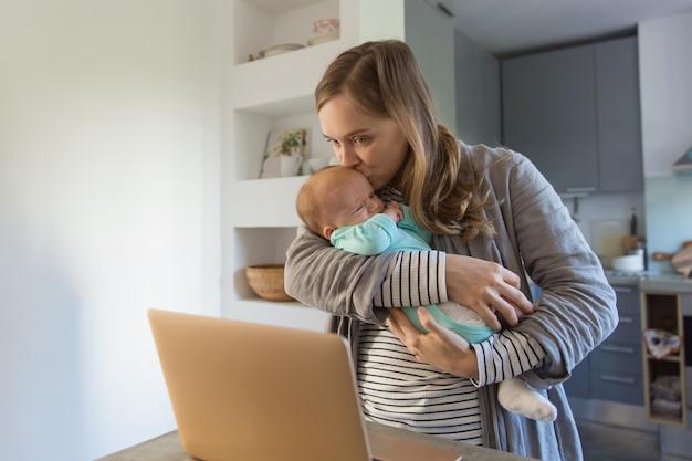 Nova mãe assistindo filme no laptop