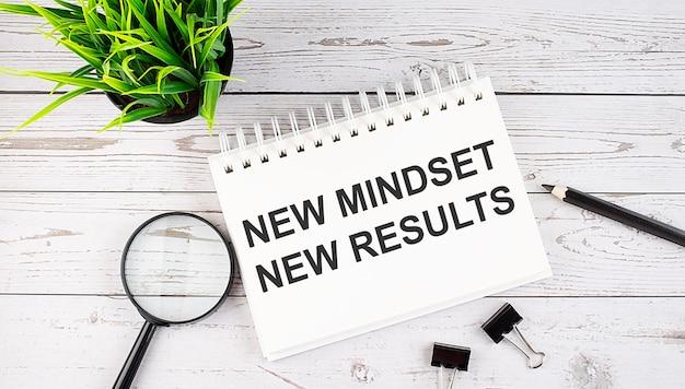 Nova mentalidade, novo resultado, conceito de texto escrito no caderno com ferramentas de escritório no fundo de madeira