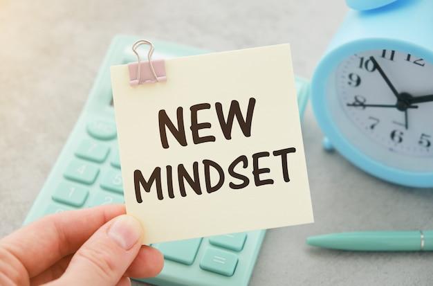 Nova mentalidade - novo texto de resultados em notas adesivas isoladas na mesa do escritório
