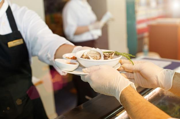 Nova mesa normal de restaurante enviada para a mesa do cliente com luvas limpas