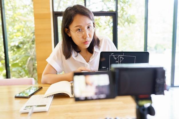 Nova mulher asiática normal com idades entre 30 e 35 anos, apresentação de treinador vlogger treinando pessoas on-line.