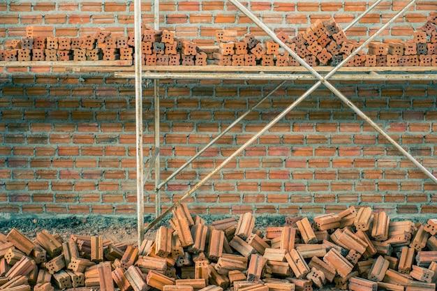 Nova parede de tijolo vermelho interior com andaimes sob fundo de textura de construção.