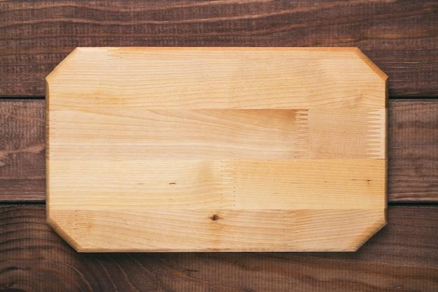 Nova placa de corte de madeira retangular no fundo da mesa de madeira. vista do topo. maquete para projeto de alimentos.
