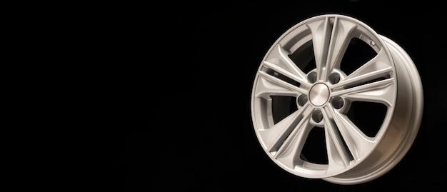 Nova roda de liga de alumínio, cor prata em uma parede preta. copie o espaço