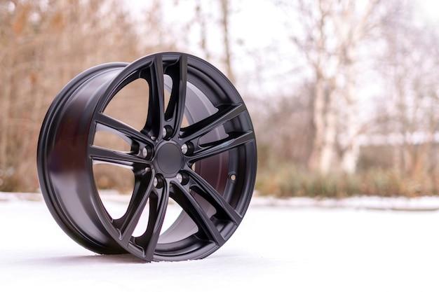 Nova roda de liga de alumínio escovado preta elegante, na neve branca. inverno. serviços de ajuste automático