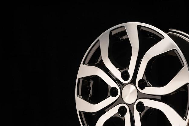 Nova roda de liga leve do carro, close-up em uma parede preta, raios de roda. belo design. copie o espaço