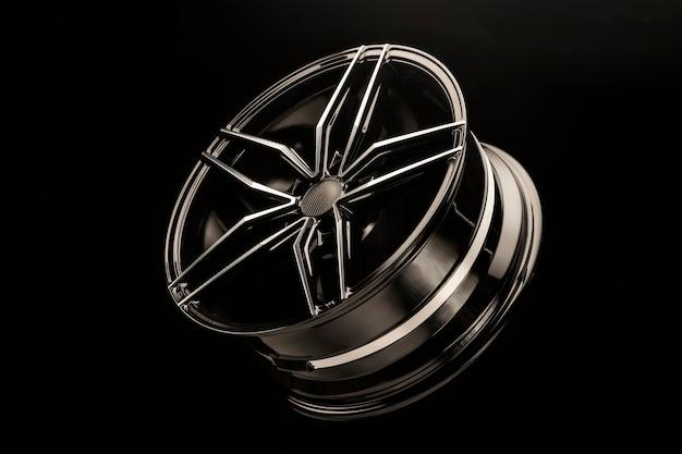 Nova roda de liga leve esportiva forjada preta em um fundo escuro. peso leve e design.