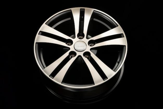 Nova roda de liga preta fosca, close-up em um fundo escuro. raios do disco com uma ranhura de prata. vista frontal.