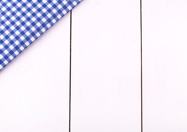 Nova toalha de mesa azul na gaiola na mesa de madeira branca