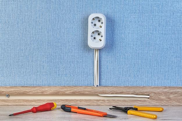Nova tomada de receptáculo duplex com chave de fenda e outras ferramentas de trabalho no chão.