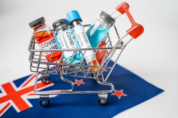 Nova vacina contra o coronavírus covid-19 no carrinho de compras na bandeira do reino unido.