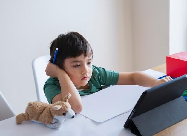 Nova vida normal, criança usando tablet aprendendo em casa, criança garoto cara séria estudando ou pesquisando ideias na internet para o dever de casa