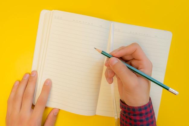 Nova vida novo capítulo. as mãos escrevem em uma folha limpa