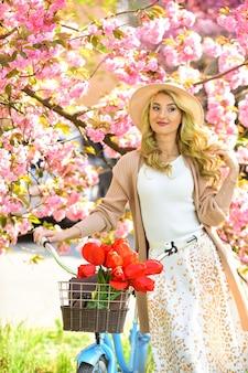 Nova vida verde. flor rosa sakura. relaxe no parque. moda e beleza. mulher andar de bicicleta vintage. garota romântica sob a flor de sakura. natureza bela temporada de primavera. cerejeira desabrochando flores.