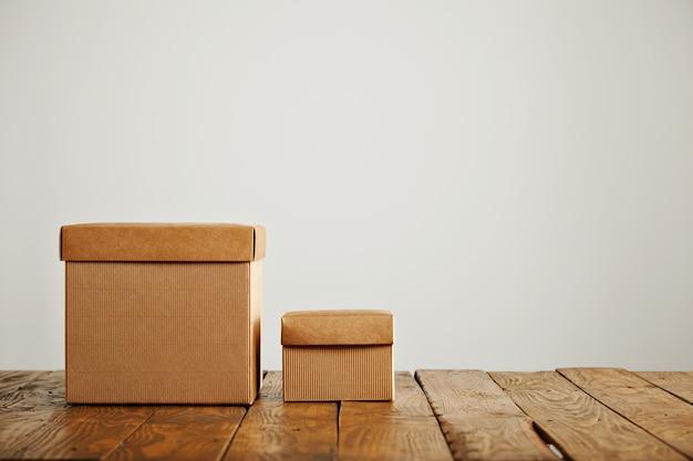 Novas caixas de papelão bege de diferentes tamanhos com tampas contrastando com a velha mesa de madeira rústica em um estúdio com paredes brancas