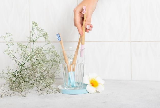 Novas escovas de dente de bambu de madeira rosa e azul em um copo de vidro no banheiro