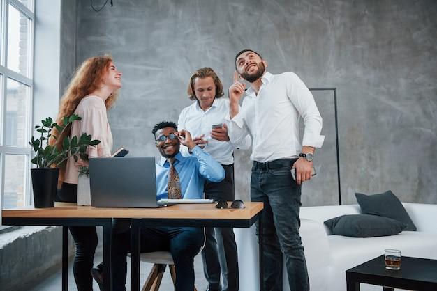 Novas idéias estão chegando. o homem gesticula. grupo de trabalhadores de escritório multirracial em roupas formais falando sobre tarefas e planos