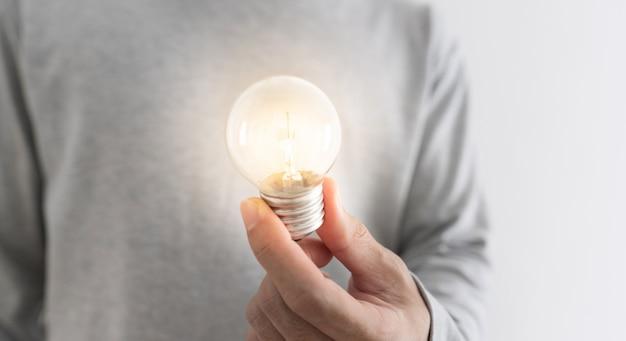 Novas idéias, inovação e conceito de inspiração. um homem segurando a lâmpada incandescente por lado