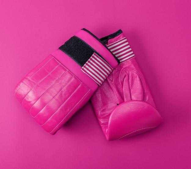 Novas luvas de boxe de couro rosa esporte em um fundo rosa