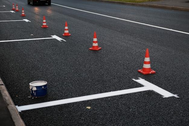 Novas marcações viárias em estacionamento de asfalto em faixa de rodagem ao longo da estrada trabalho manual processo de pintura