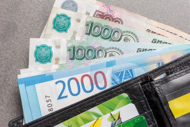 Novas notas russas nas denominações de 1000, 2000 e 5000 rublos e cartões de crédito em um close de bolsa de couro preto