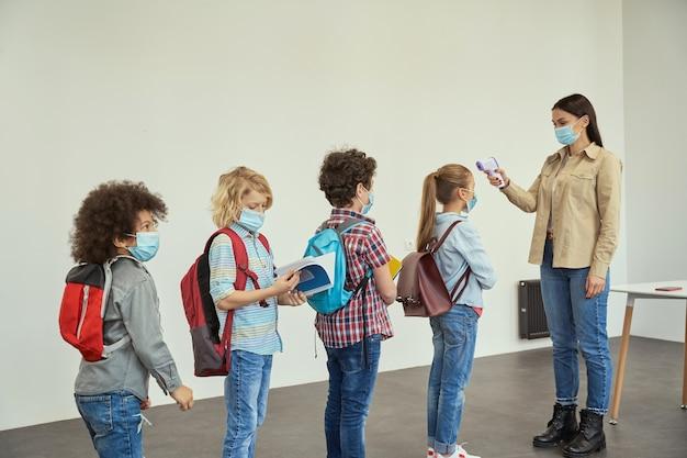 Novas regras, uma jovem professora moderna medindo a temperatura da triagem de crianças com termômetro digital