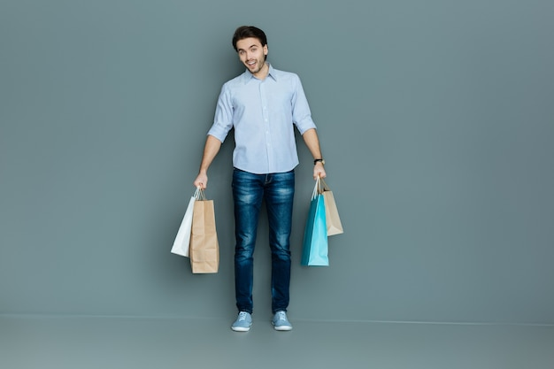 Novas roupas. homem simpático e alegre sorrindo e segurando sacolas enquanto vai às compras