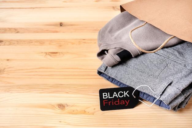 Novas roupas masculinas em um saco de papel com uma etiqueta preta de sexta-feira em uma mesa de madeira com mete para texto.