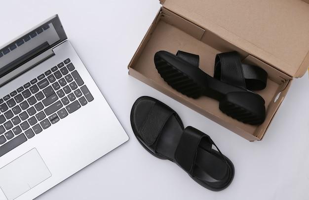 Novas sandálias em uma caixa e um laptop em um fundo branco. vista do topo