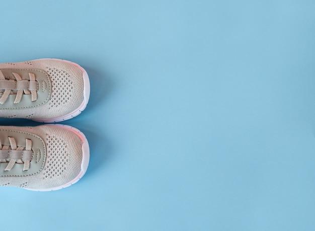 Novas sapatilhas cinza sobre fundo azul pastel