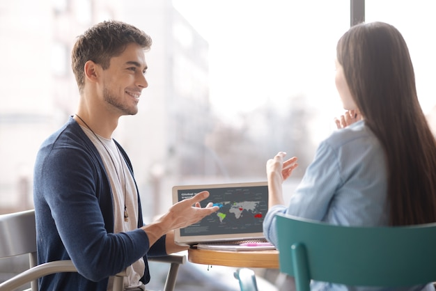 Novas tendências de negócios. homem jovem e bonito apresentando algumas informações de negócios para sua colega enquanto está sentado à mesa perto da janela.